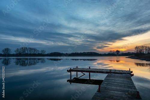 Fototapeta Wooden fishing pier and beautiful evening clouds over the lake, Stankow, Poland obraz