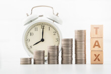 Concept Of Tax Season With Wooden Blocks, Coins And Alarm Clock.