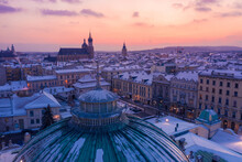 Snowy Winter In Krakow Poland Aerial View. City Center Old Town, Roof Of Juliusz Slowacki Theatre, And Rynek Glowny With St. Mary's Basilica And Town Hall Tower On Background.