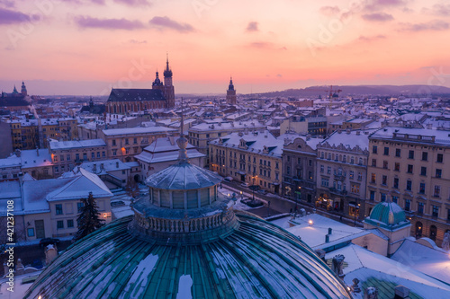 Fototapeta Snowy winter in Krakow Poland aerial view. City center old town, Roof of Juliusz Slowacki Theatre, and Rynek Glowny with St. Mary's Basilica and Town Hall Tower on background. obraz