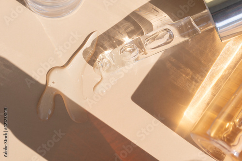 Fototapeta close up of pipette with pouring liquid serum with golden bottle and shadows obraz