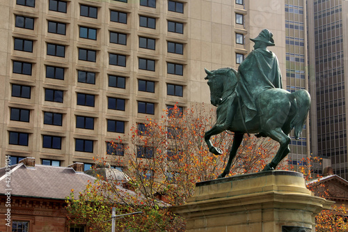 Obraz Sydney, NSW Australia. High-rise Sydney hotel, sandstone buildings and a of bronze statue features King Edward VII in uniform on horseback looking at the hotel - fototapety do salonu