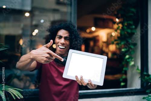 Obraz Millennial generation man with blank touch pad pointing on mock up screen display with copy space area for social publication with advertising, blurred male blogger showing gadget notification for app - fototapety do salonu