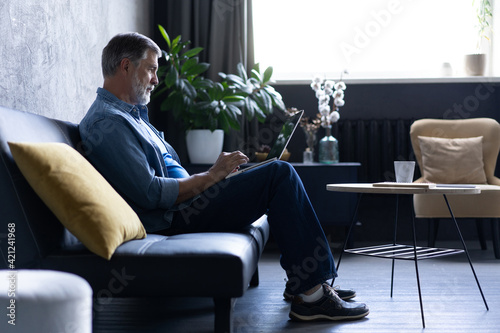 Smiling mature man sitting on a sofa typing on a laptop in a living room. Working from home in quarantine lockdown