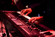 A Musician Plays A Musical Instrument Or Synthesizer On A Concert Stage.