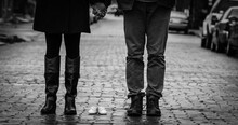 Low Section Of Husband And Wife Standing With Baby Shoes On Street