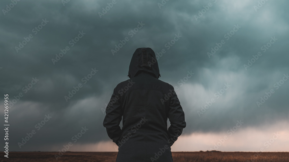 Fototapeta Rear view of female person wearing hooded jacket against dark moody dramatic clouds at sky