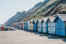 Unidentifiable People In The Distance, Walking By Colourful Beach Huts In Sheringham, Norfolk, Uk.