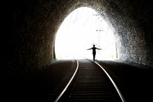 Silhouette Of A Girl Coming Out Of The Tunnel. Light At The End Of The Tunnel. Stone Walls. Railway Rails In The Foreground.