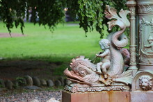 Close-up Of Cherub On Fish Statue In Park