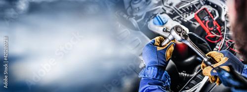 Fotografia, Obraz Auto mechanic working on car broken engine in mechanics service or garage