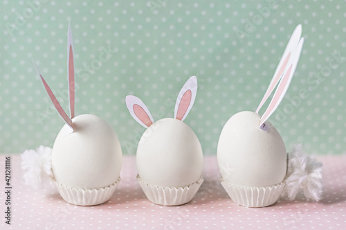 White chicken eggs with bunny ears and tails on bed flowers background. A family. Happy Easter holiday concept