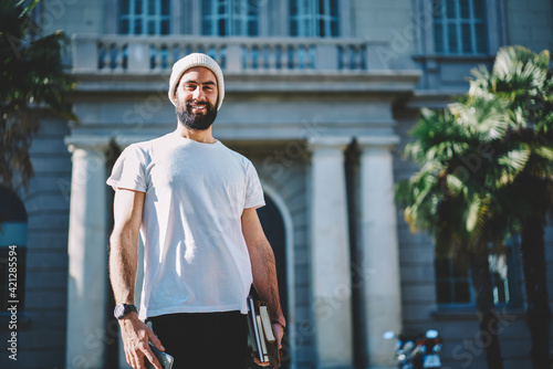 Obraz Half length portrait of cheerful Turkish student in hat smiling at camera holding education equipment in hand, happy Middle Eastern male with textbooks posing at street urban setting on leisure - fototapety do salonu