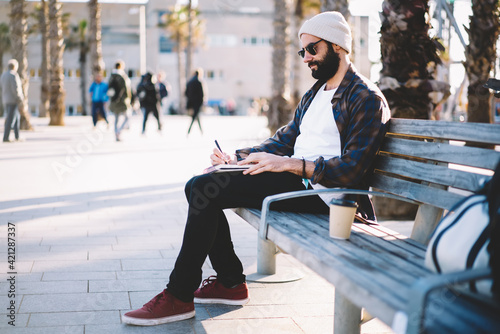 Fototapeta Talented Turkish male poet writing text ideas in copybook for creating articles, Middle Eastern hipster guy in sunglasses spending leisure daytime for note travel impression to personal diary obraz