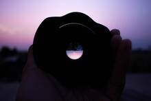 Cropped Hand Of Person Holding Camera Lens During Sunset