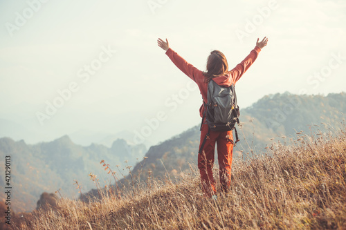 A woman traveler in sportswear with a backpack stands on a mountainside and meets the dawn with her hands up Wallpaper Mural