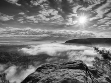 Landscape View. Exposed Sandstone Cliff Above Deep Misty Valley In Saxony Switzerland. Dreamy Mood