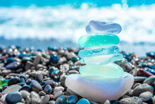 Sea Glass Stones Arranged In A Balance Pyramid On The Beach. Beautiful Azure Color Sea With Blurred Seascape Background. Meditation And Harmony Concept.