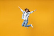 Full Length Of Young Overjoyed Excited Fun Expressive Student Happy Woman 20s Wearing Denim Shirt White T-shirt With Outstretched Hands Jump High Isolated On Yellow Color Background Studio Portrait