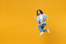 Full Length Of Young Excited Fun Expressive Fast Sporty Student Woman 20s Wear Casual Stylish Denim Shirt White T-shirt Run Jump High Hurrying Up Isolated On Yellow Color Background Studio Portrait