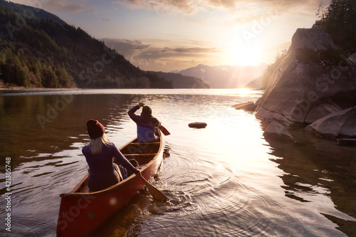 Fotografering Couple friends canoeing on a wooden canoe during a colorful sunny sunset