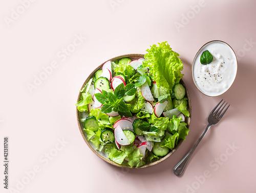 Fototapeta Vegan vegetarian healthy fresh vegetable salad of green lettuce, radish and cucumber