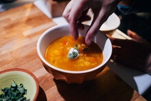 High Angle View Of Hand Preparing Soup In Bowl On Table