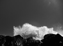 Low Angle View Of Waves Splashing On Rocks Against Sky
