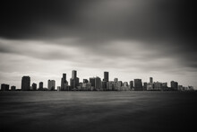 City Skyline By Sea Against Cloudy Sky