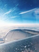 Airplane Flying Against Blue Sky Seen Through Window