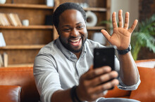 Portrait Photo Of Smart Black African Guy Waving Hand Looking At Camera, Using Video Call Communicate With Business Colleague, Friend From Home, During Self Isolation From Coronavirus Outbreak Crisis