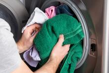 Cropped Hand Of Man Putting Clothes In Washing Machine