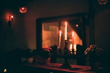 Close-up Of Illuminated Candles On Table At Home