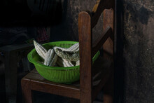 High Angle View Of Plastic Green Basket Filled With Esrs Of Corn Resting On Kitchen Chair