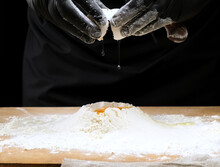 Male Chef In Black Uniform And Black Latex Gloves Breaks A White Hen's Egg Into A Pile Of White