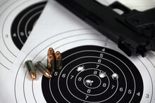 Gun And Many Bullets Shooting Targets On White Table In Shooting Range Polygon. Training For Aiming And Shooting