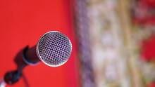 Close Up Of Microphone In Concert Hall Room On Red Background Concept.