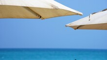Two Beach Umbrellas Close Up By Sea And Sky