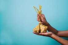Midsection Of Person Holding Ketupat Or Rice Pack In Woven Coconut Leaves Against Blue Background
