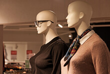 Two Mannequins Wearing The Latest Autumn Fashion And Glasses