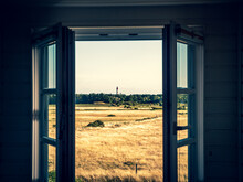 Scenic View Of Field Seen Through Window With Lighthouse