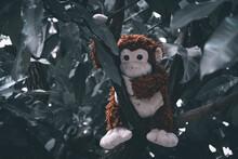 A Stuffed Monkey Laying Down On A Branch Of A Mango Tree
