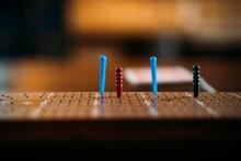 Multicoloured Pegs On Crib Board, Eye Level.