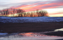 Sunset Over A Field Of Melting Snow