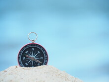 Compass On Sand In Blue Sea  Background.