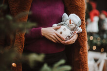 Midsection Of Woman Holding Snowman Against Blurred Background