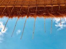 Directly Below Shot Of Thatched Roof Parasol Against Blue Sky