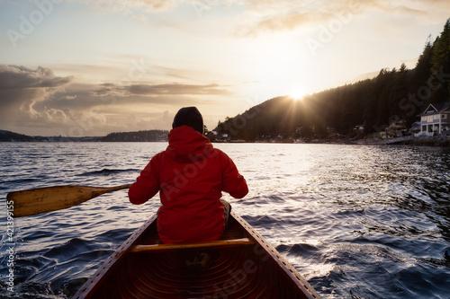Fotografiet Adventure Man on a wooden canoe is paddling in the ocean