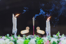 Close-up Of Lit Candles And Incense In Temple