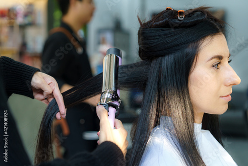 Asian hairdresser curls hair for customer with ceramic curler at beauty salon..